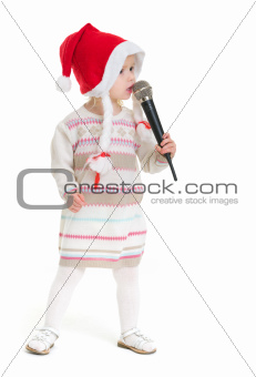 Baby girl in Christmas hat singing into microphone