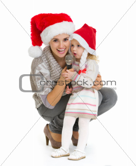 Christmas portrait of happy mother and baby girl singing into microphone