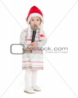 Baby girl in Christmas hat using microphone