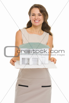 Smiling architect woman showing scale model of house