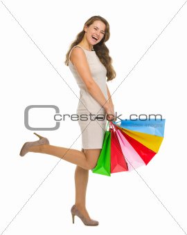 Smiling young woman in dress with shopping bags