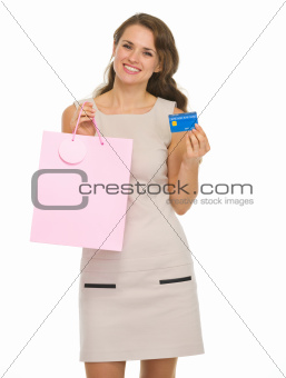 Smiling young woman with shopping bags and credit card