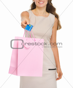 Closeup on shopping bags and credit card in woman hand