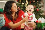 Young Attractive Ethnic Woman With Her Newborn Baby Near The Christmas Tree.