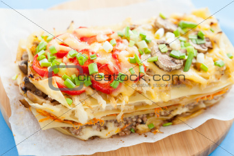 Freshly baked homemade lasagna on a wooden kitchen board