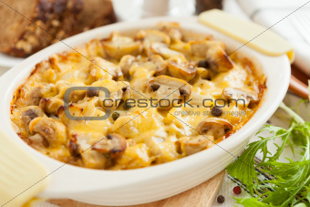 Baked mushrooms, potatoes and cheese closeup