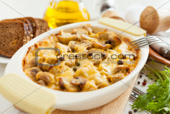 Vegetables casserole with mushrooms, potatoes and cheese closeup