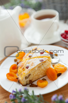 Cheese cake with tea, dried apricot and raisins closeup on a pla