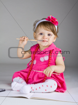 Seated little girl holding a paintbrush
