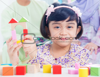 Child building wooden house