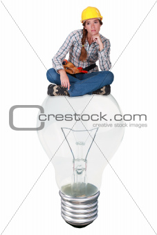 Female laborer sitting on a light bulb