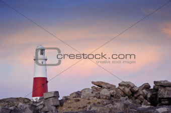 Victorian lighthouse on promontory of rocky cliffs,