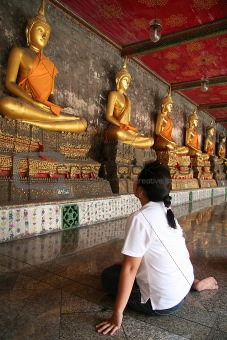 A girl watching status of golden buddha inside Wat Suthad temple