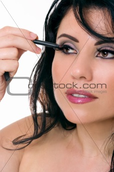 Beautiful woman applying eye pencil