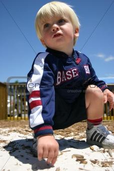 Blonde boy playing in sandy playground