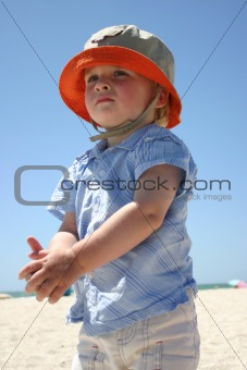 Blonde boy standing on sunny beach