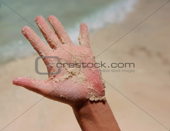 a white wet sand in sunburned hand