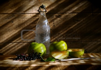 Old bottle with green apples