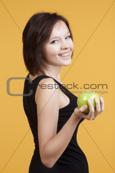 teenage girl holding a green apple smiling - isolated on yellow