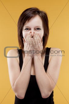 surprised teenage girl covering mouth with her hands looking, laughing - isolated on yellow