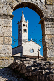 White Church Framed in the Arch of Ancient Roman Amphitheater
