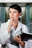 Thinking medical doctor with stethoscope. Over hospital backgrou