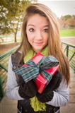 Pretty Festive Smiling Woman with Wrapped Gift with Bow Outside.