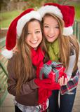 Two Attractive Festive Smiling Mixed Race Women Wearing Christmas Santa Hats Holding a Wrapped Gift with Bow Outside.