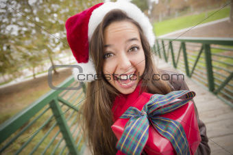 Pretty Festive Smiling Woman Wearing a Christmas Santa Hat with Wrapped Gift and Bow Outside.
