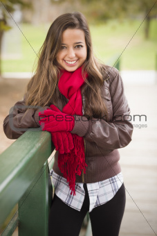Pretty Festive Smiling Woman Portrait Wearing a Red Scarf and Mittens Outside.