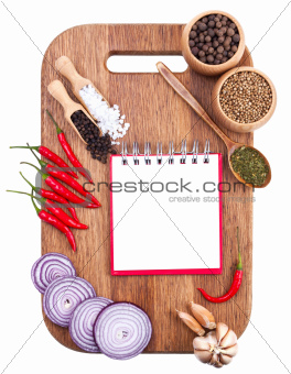 Open notebook and fresh vegetables on an old wooden cutting boar