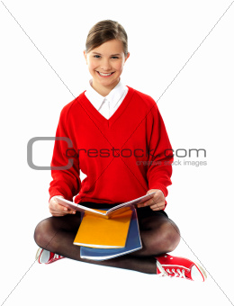 Pretty school girl seated on floor, holding book