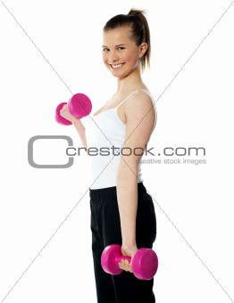 Strong teenager working out with dumbbells