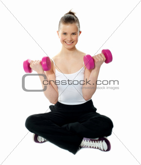 Smiling young girl lifting weights