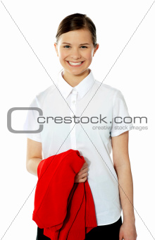 School girl holding her red sweater and smiling