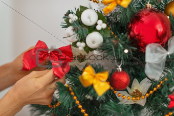 Closeup on woman hand decorating Christmas tree