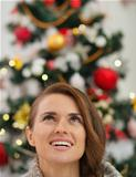 Woman in front of Christmas tree looking up