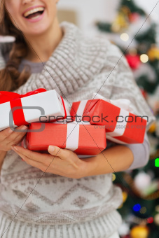 Closeup on Christmas present boxes holding by happy woman