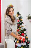 Happy woman with present box near Christmas tree