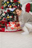 Happy woman putting present box under Christmas tree