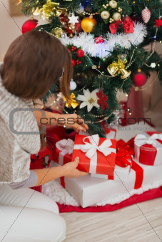Woman putting present box under Christmas tree