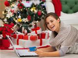 Happy woman with laptop near Christmas tree making online purchases