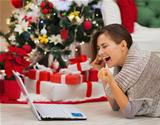 Happy woman with laptop near Christmas tree rejoicing success