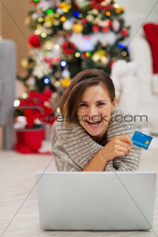 Smiling woman with laptop and credit card near Christmas tree