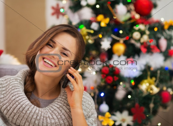 Happy woman near Christmas tree making phone call