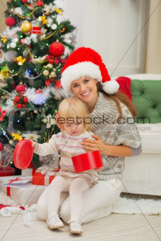 Smiling mother holding baby opening Christmas present box