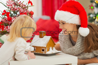 Happy mother and baby looking on Christmas Gingerbread House