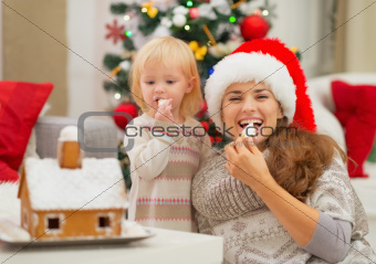 Happy mother and baby eating Christmas cookies