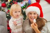 Smiling mother and baby eating Christmas cookies