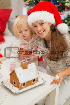 Portrait of smiling mother and baby near Christmas Gingerbread house